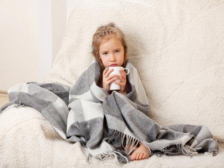 Ребенок пьет чай в кровате
