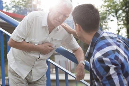 Парень помогает пожилому мужчине с одышкой