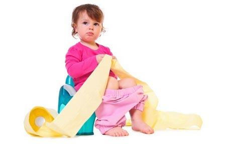 Ребенок держит туалетную бумагу и сидит на горшке