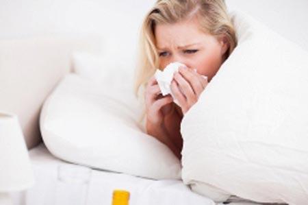 Девушка лежит в кровати и вытирает нос
