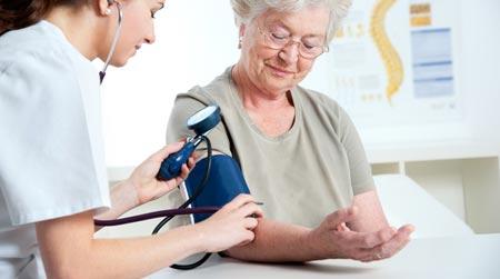 Медсестра меряет давление пожилой женщине